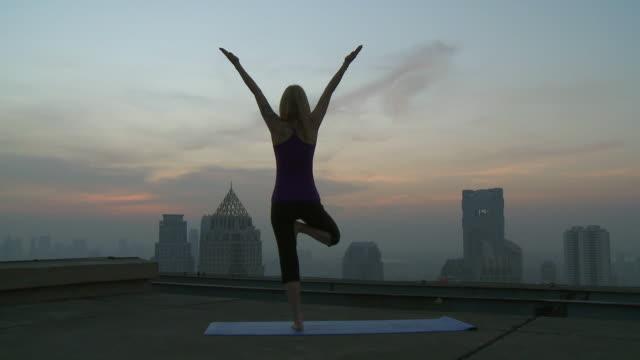 WS PAN Woman doing yoga movements on rooftop / Bangkok, Bangkok, Thailand