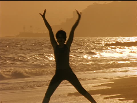 SILHOUETTE woman doing yoga on beach at sunset / Los Angeles