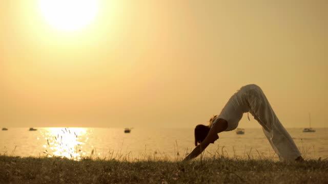 HD: Woman Doing Yoga On The Beach