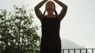 MS LA Woman doing yoga standing against sun / Ravello,Campania