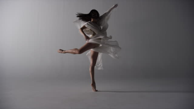 woman draped with silk runs elegantly towards camera then performs pirouettes