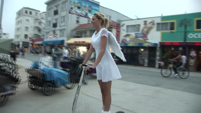 WS PAN Woman dressed in angel costume riding motor scooter/ Venice Beach, California