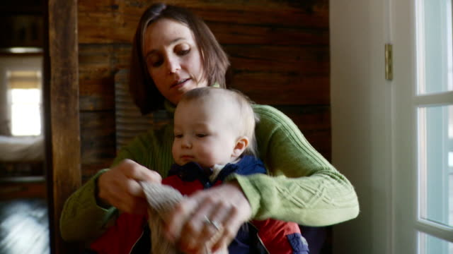 MS Woman dresses baby in winter jacket / Stowe, Vermont, United States