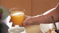 Woman drinking fresh-squeezed orange juice at breakfast