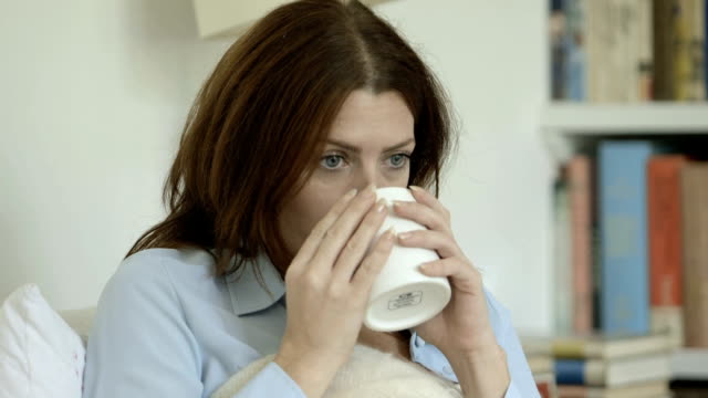 Woman drinking from mug on sofa.