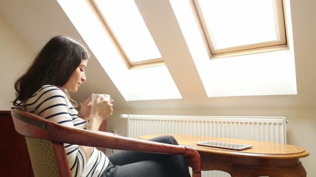 Vrouw haar koffie drinken terwijl u geniet van een zonnige ochtend bij het raam.