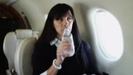 MS Woman drinking water from bottle in airplane / Spanish Fork, Utah, USA