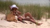 MS Woman drinking water from bottle sunbathing on lounge chair on beach, Eastville, Virginia, USA