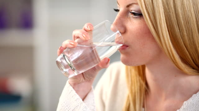 Woman drinking water,closeup.