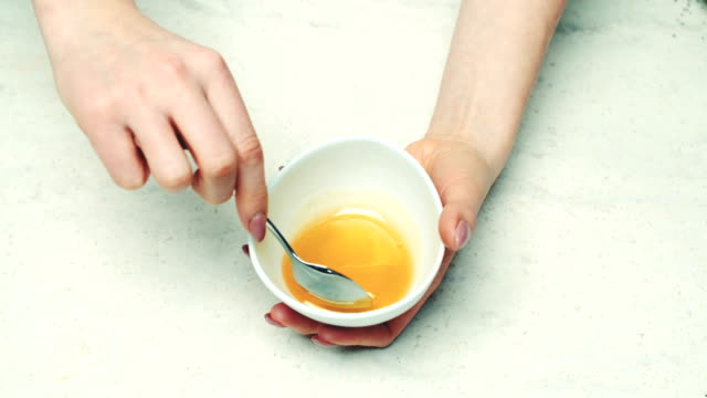 Woman Dripping Honey From Spoon Into Bowl