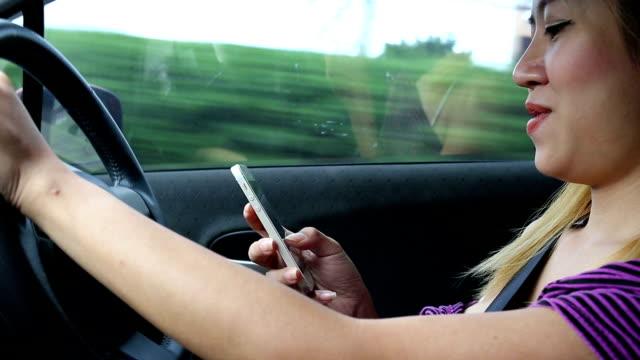 kvinna drivrutinen med hjälp av en mobiltelefon