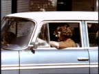 / woman driving 1960 Rambler wagon across town encounters other slow drivers and traffic / old man slowly driving in front of woman in a 1954 Ford...