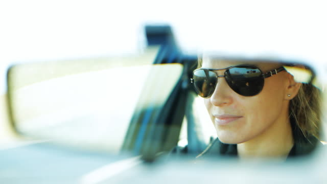 Woman driving a car in sunglasses