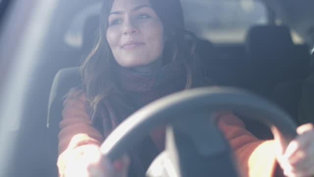 Woman driving car listening to music