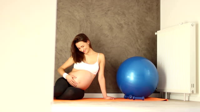 Woman during pilates in pregnancy at home