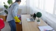 Woman dusting desk near laptop