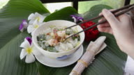MS Woman eat shrimp with chopsticks from noodle soup / Mae Nam, Ko Samui, Thailand