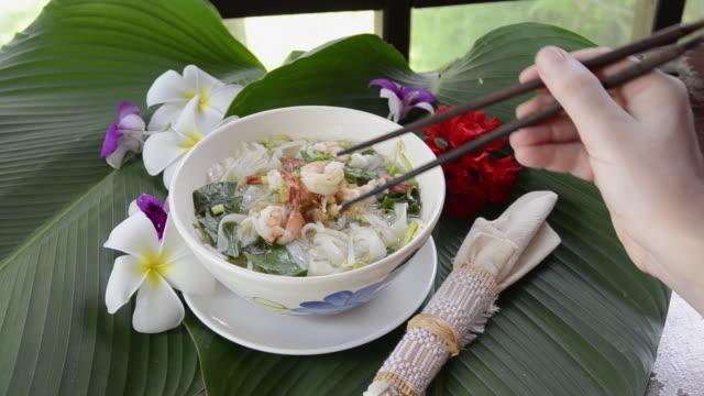 MS Woman eat shrimp with chopsticks from noodle soup / Mae Nam, Ko Samui, Thailand