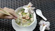Woman eat shrimp with chopsticks from noodle soup