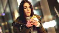 Woman eating burger at the street