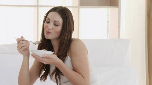 MS Woman eating cereal, sitting on bed / Cape Town, Western Cape, South Africa