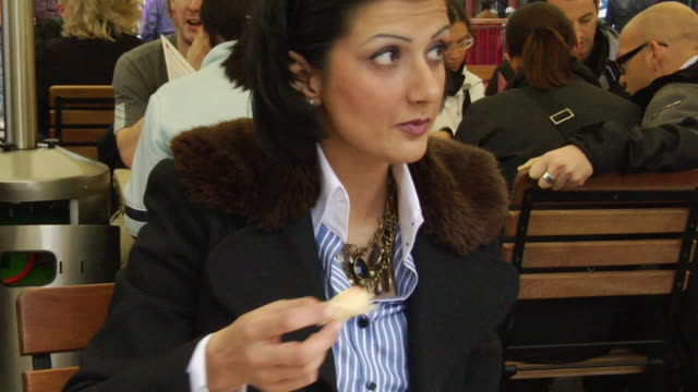 CU, Woman eating croissant in outdoors cafe, Covent Garden, London, England
