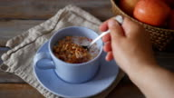 Woman eating granola with milk