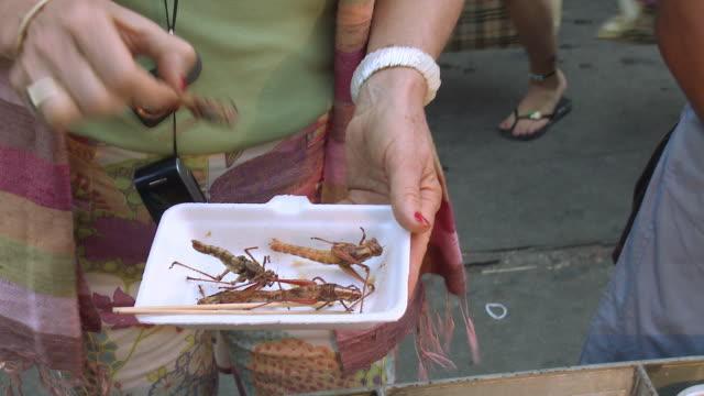 CU TU Woman eating grasshopper in busy city street, Bangkok, Thailand
