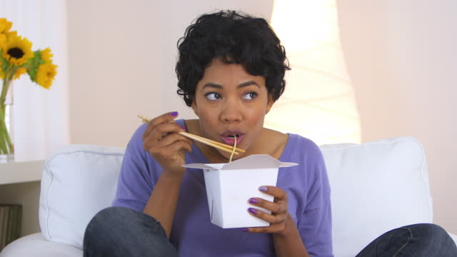 woman eating up noodles from Chinese take out