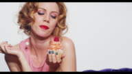 A woman eats the icing of a cupcake with her finger