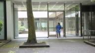 WS PAN Woman emerging from office building onto urban park walkway / Portland, Oregon, USA