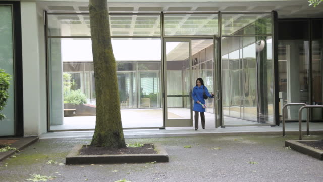 WS PAN Woman emerging from office building onto urban park walkway / Portland, Oregon, USA
