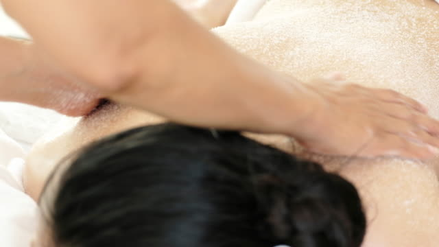 Woman enjoying a salt scrub massage for relax.
