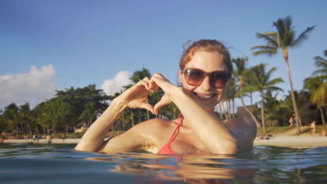 Vrouw genieten in de zee vormen een hart met handen