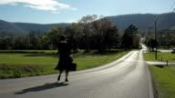 Woman enjoying outdoor life walking on sunny path