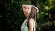 Woman enjoys summer rain on her face