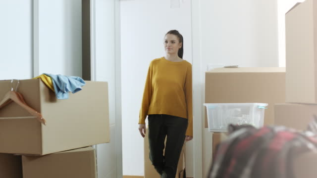 Woman entering in her new apartment full of cardboard boxes