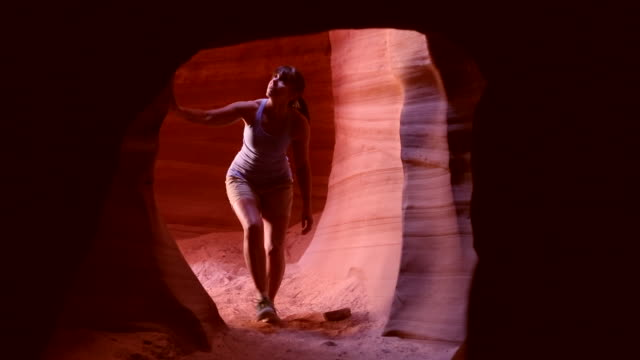 A woman enters a cave in Canyon X near Page, Arizona.