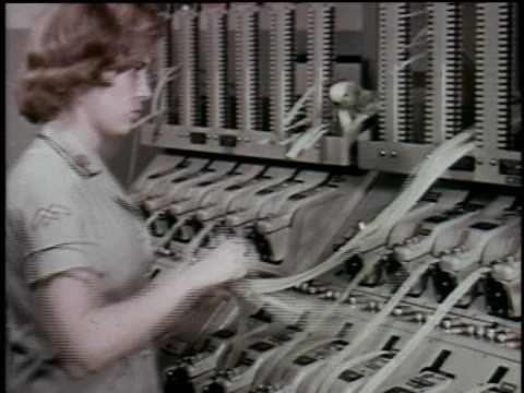1965 MONTAGE Woman examines ticker tape and man pulls out drawer filled with film equipment