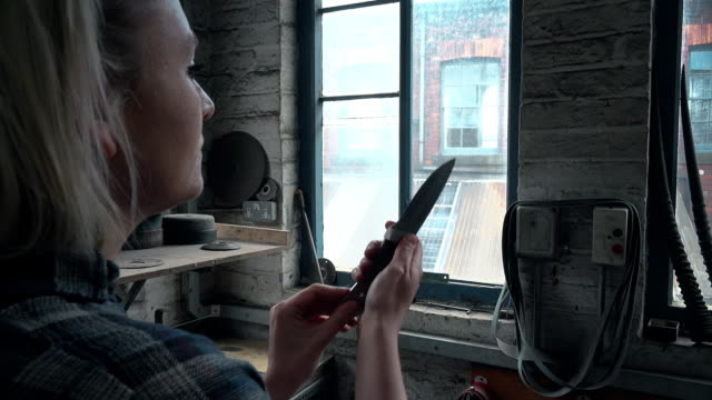 Woman examining knife