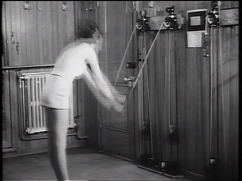 B/W 1934 woman excercising with weight machine in cruise ship gym + looking at camera
