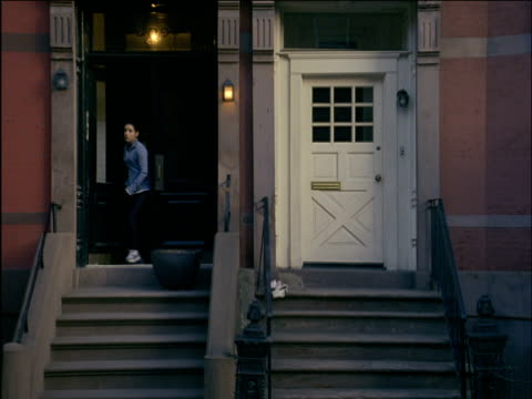 WS Woman exiting her apartment and jogging down steps / Brooklyn, New York, USA