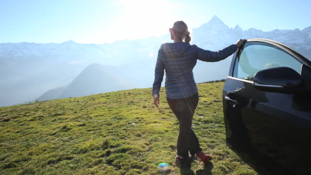 Woman exits car door into meadow, looks out to mountains