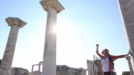 Woman explores monument ruins, looks up to columns