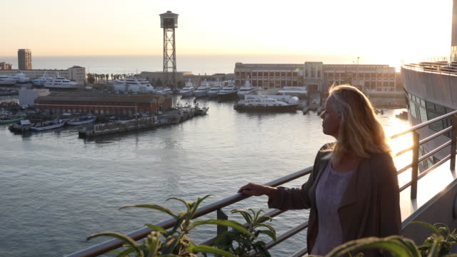 Woman explores seafront harbour area of city, Barcelona