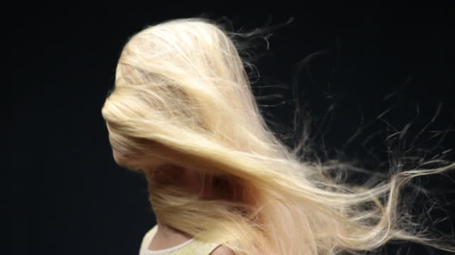 CU SLO MO Woman face covered with blond and hair moving in wind / London, Greater London, United Kingdom