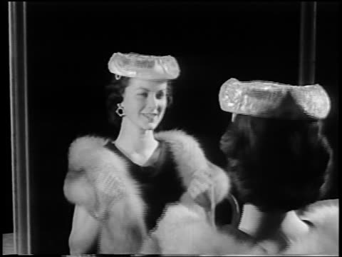 B/W 1956 woman facing mirror modelling plastic crown-like hat / newsreel