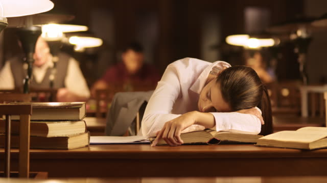 DS Woman falling asleep over books in the library