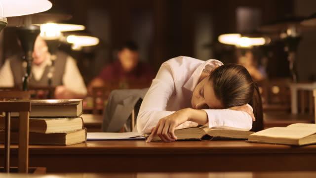 DS Frau Schlafen auf Bücher in der Bibliothek auf der Vorderseite