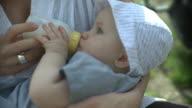 CU Woman feeding daughter (6-11 months), outdoors, New York City, New York, USA